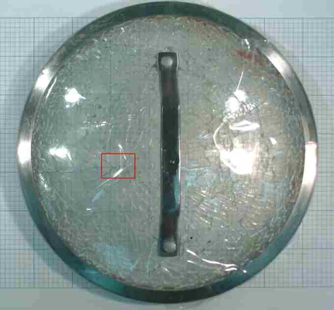 Fractured glass lid - fracture origin outlined